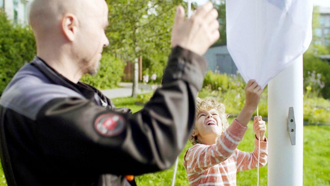 Kiinteistönhoitaja nostaa Suomen lippua yhdessä pienen pojan kanssa kiinteistön pihalla.