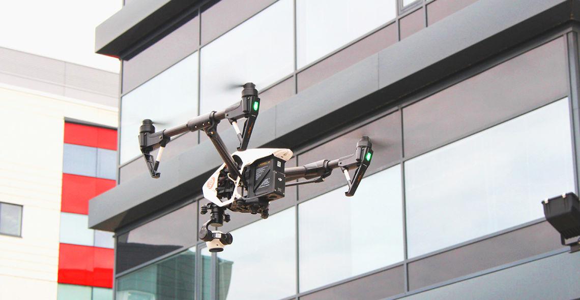 Ilmakuvauskopteri kuvaa korkean kiinteistön ulkoseinän kuntoa.