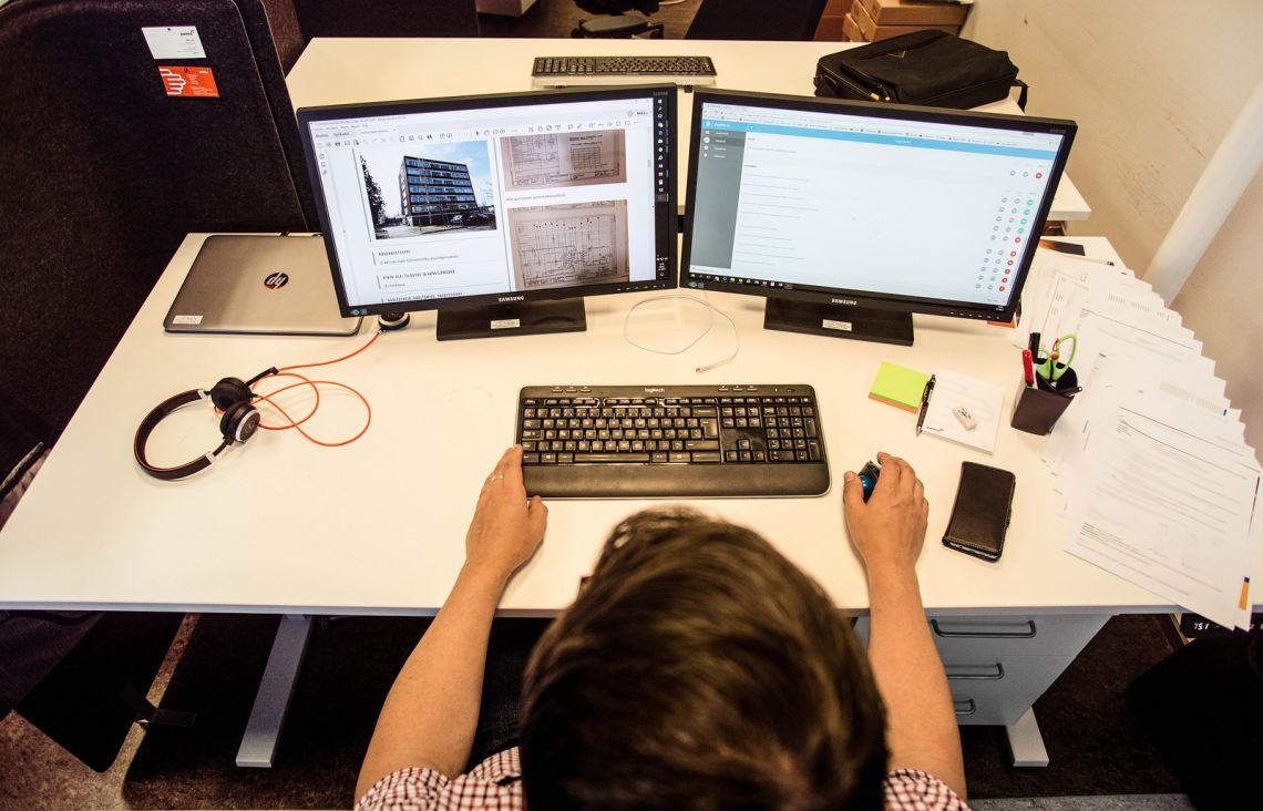Työntekijä tarkkailee tietokoneen ruuduilta eri tilojen energiankulutusta.