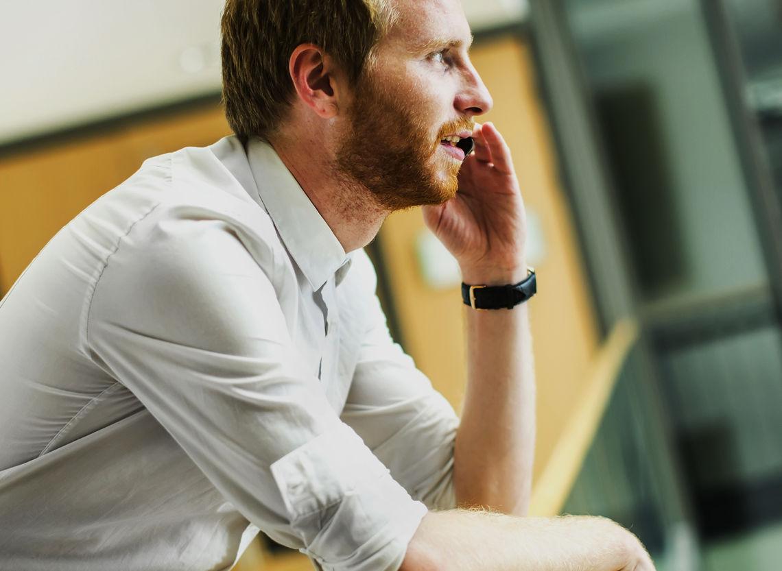 Insinööri puhuu puhelua business parkin avoimessa rappukäytävässä.