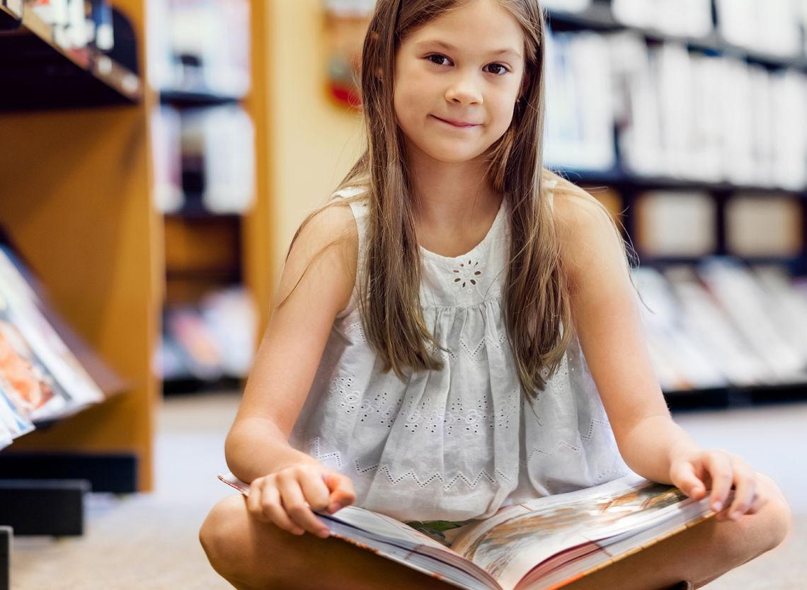 Pieni tyttö istuu kirjaston puhtaalla lattialla lukemassa kirjaa.