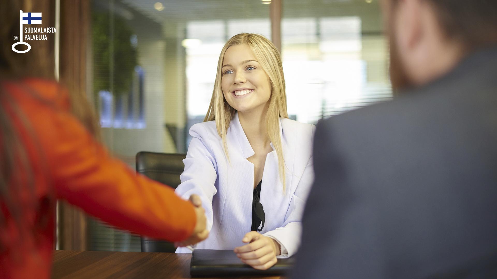 Nuori nainen hymyilee iloisesti ja kättelee työsopimuksen teon johdosta.