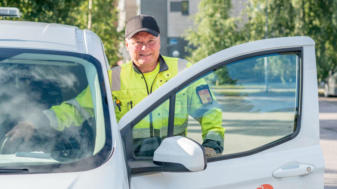 Palveluohjaaja Ari Murto kuvassa työautoon astumassa, auton ovi on auki ja taustalla näkyy vehreät koivut.