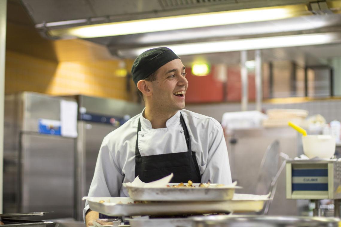 Kuvassa Simo Korvepää hymyilee työpisteen keittiössä.