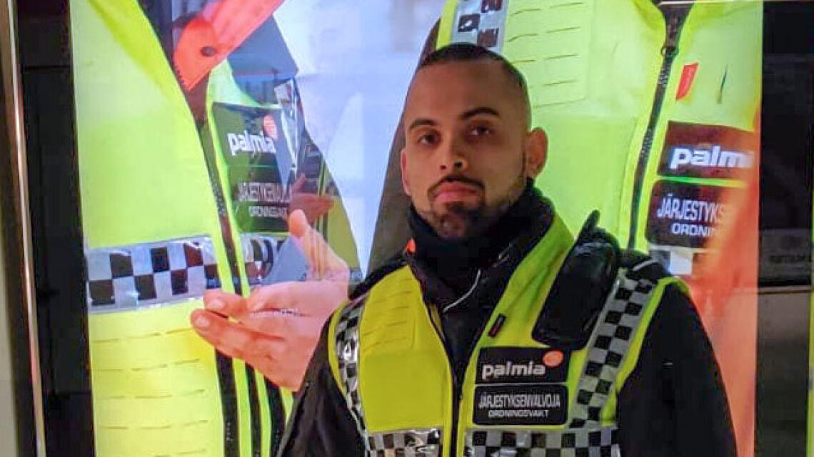 Palmian järjestyksenvalvoja Khan Burhan poseeraa metroasemalla mainosnäytön edessä, mainosnäytöllä on Palmian mainos. Mainoksen valokuvassa Burhan poseeraa myös sama työasu päällä..