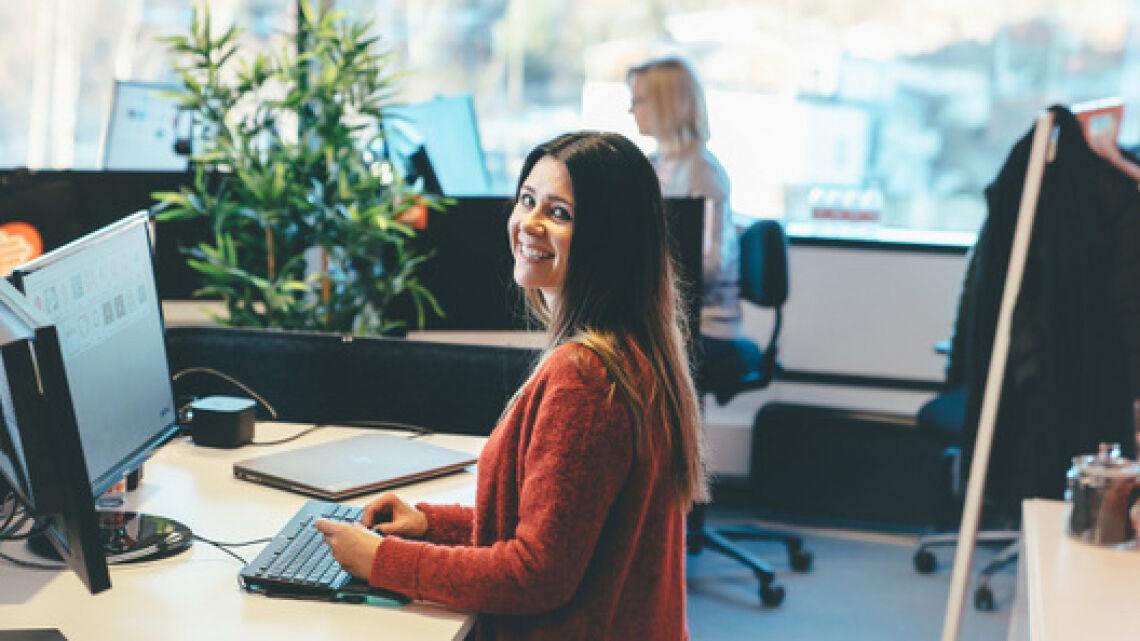 Markkinointisuunnittelija Krista Aksila-Hursti hymyilee työpisteellään Palmian toimistolla.