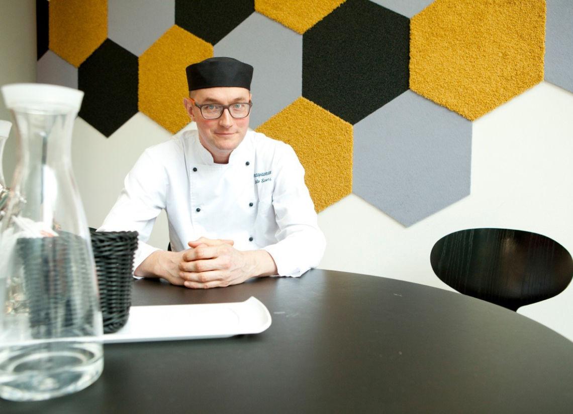 Keittiöpäällikkö Mikko Sievers istuu pöydän ääressä työasussaan.