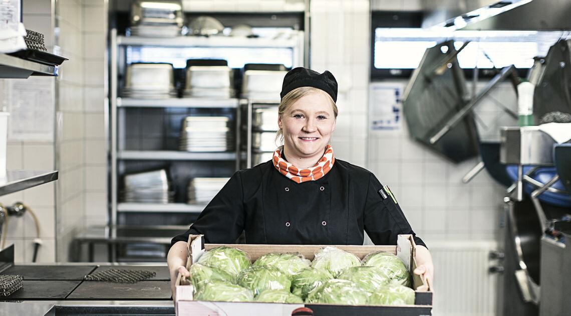 Ruokapalveluvastaava Viivi Tammisto hymyilee työpisteessä keititössä, kädessään hän pitää laatikkoa joka on täynnä tuorettaa salaattia.