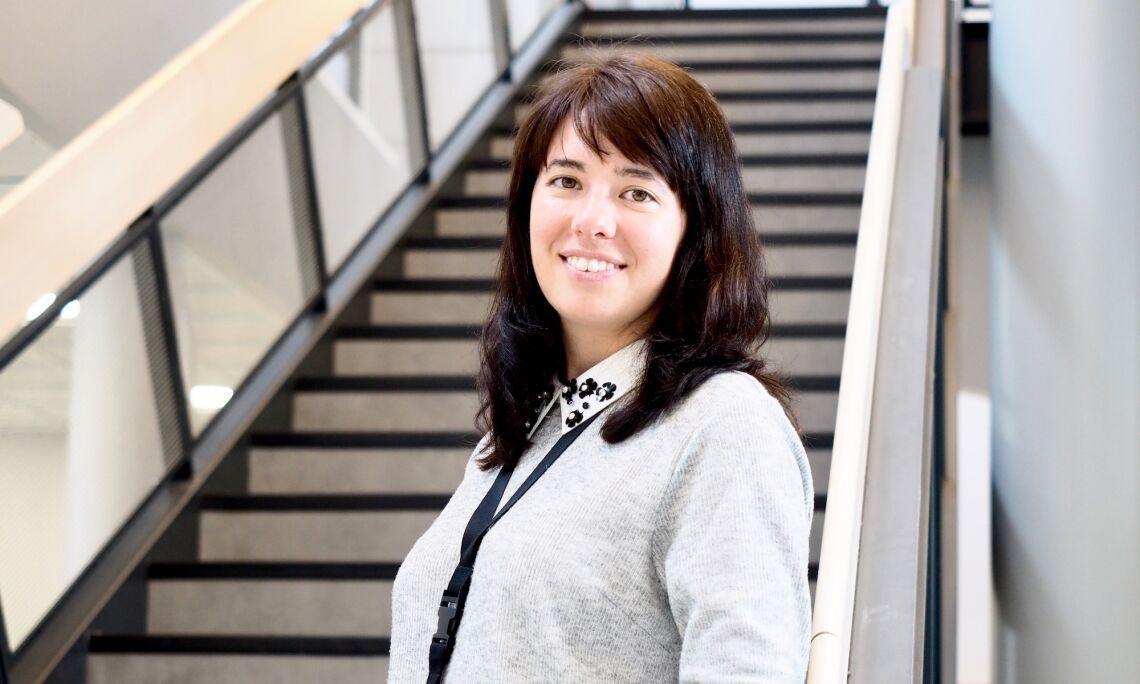 Palveluesimies Tatiana Koshcheeva hymyilee aulatilassa aurinkoisesti, taustalla korkeat portaat.
