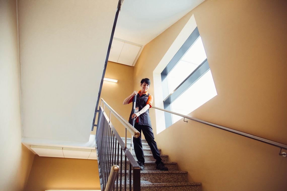 Siivooja pyyhkii lastalla rappuja portaikossa.