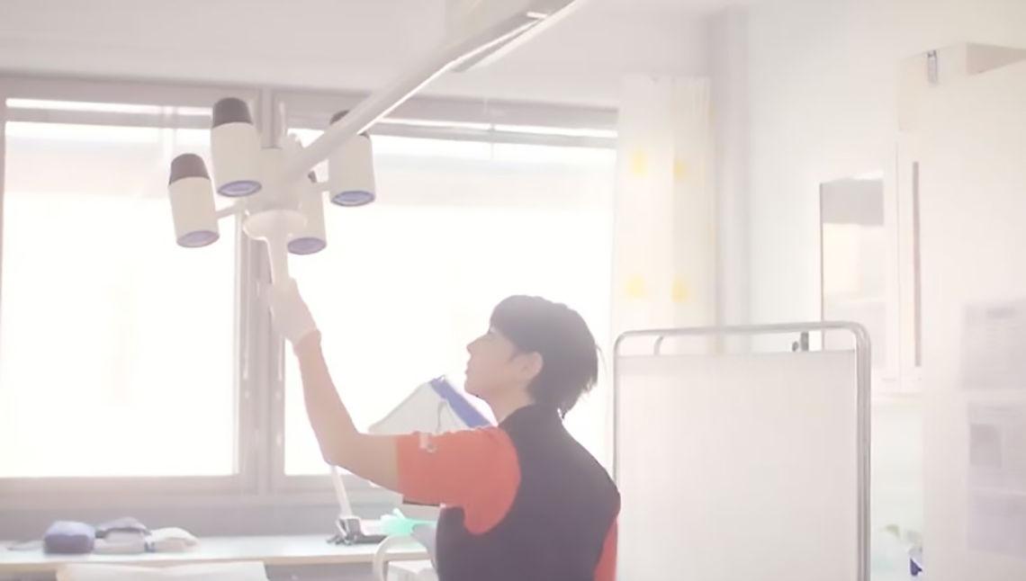 Toimitilahuoltaja puhdistaa hoitohuoneen tutkimusvalaisinta.