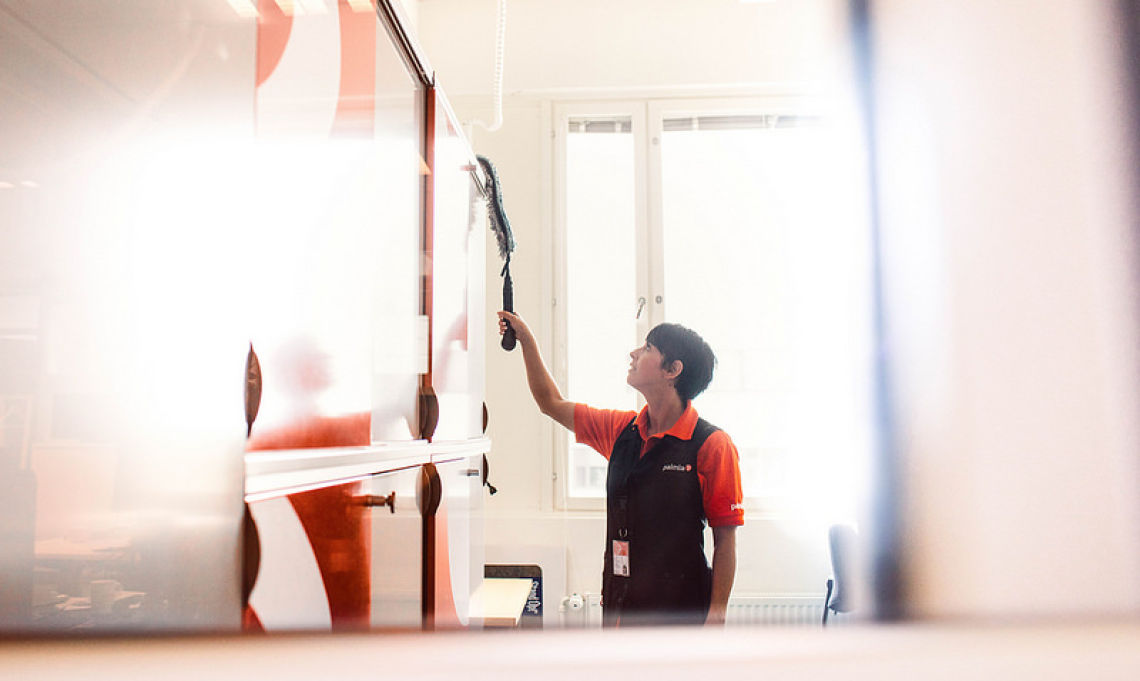 Toimitilahuoltaja siivoaa toimistossa yläpölyjä pitkävartisen pyyhkimen avulla.