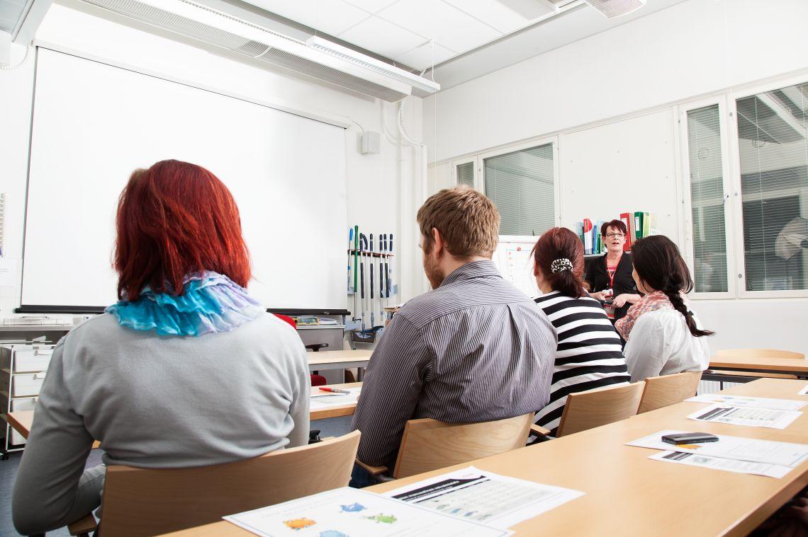 Toimitilahuoltajia istumassa koulutuksessa kokoushuoneessa.