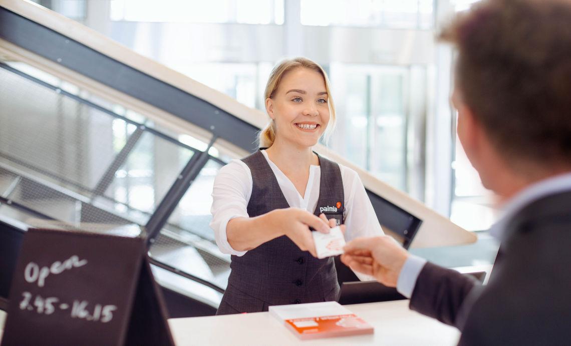 Aulapalvelija antaa business parkin asiakkaalle vierailukortin.