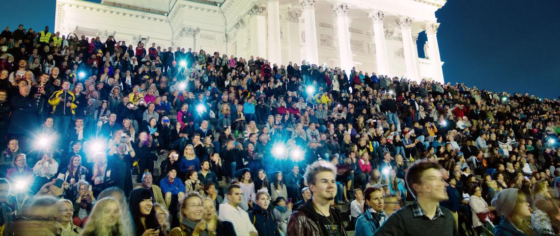 Iso ihmisjoukko juhlii uutta vuotta Tuomiokirkon portailla Helsingissä