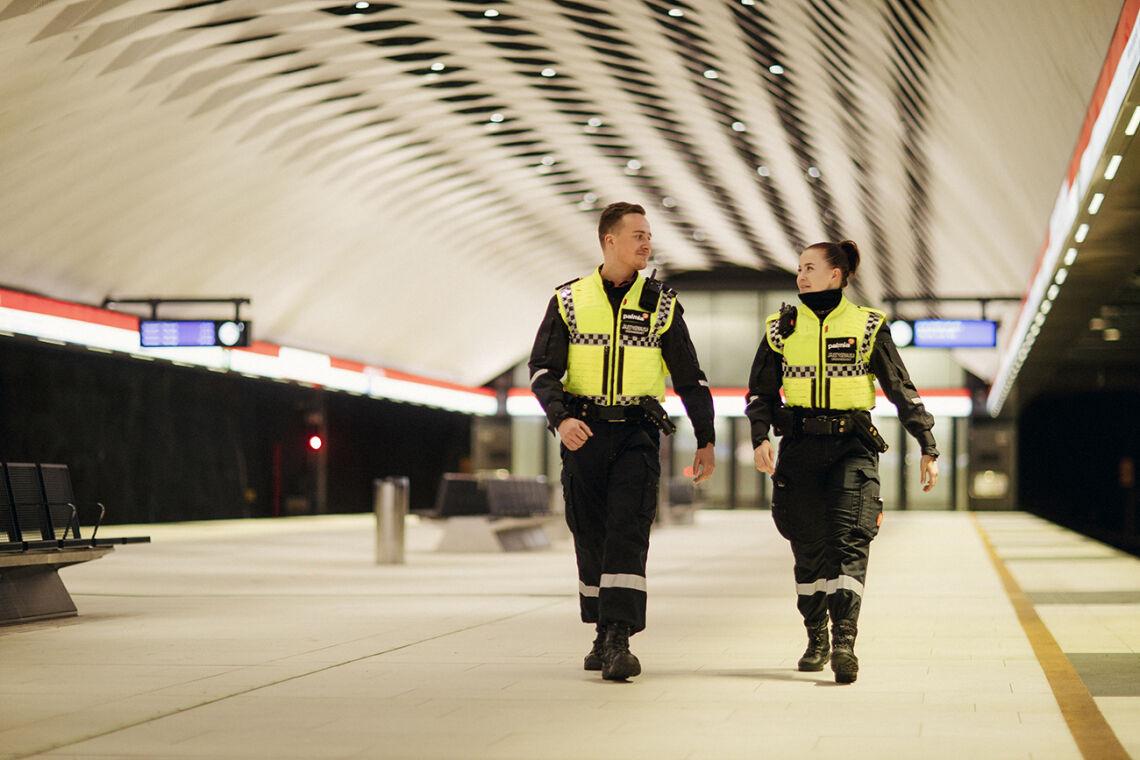 Kaksi järjestyksenvalvojaa kävelee metrolaiturilla