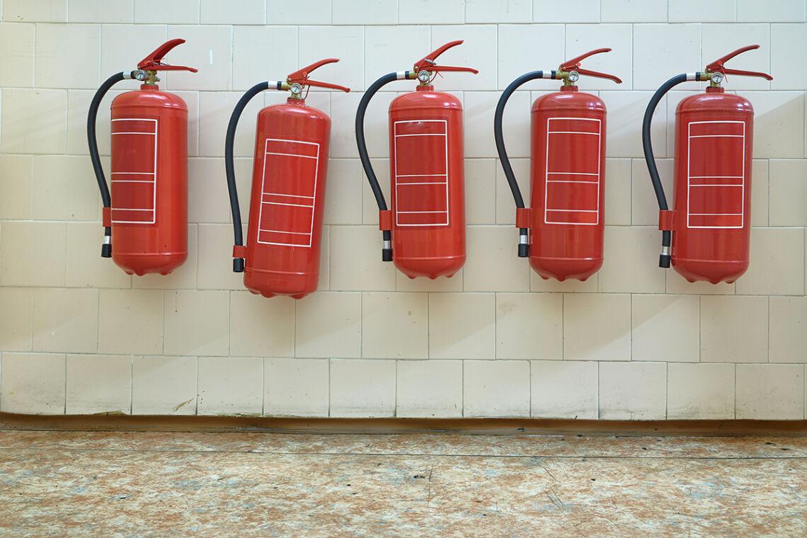 Seinällä on pitkä rivi vaahtosammuttimia, jotka tarvitsevat huoltoa.