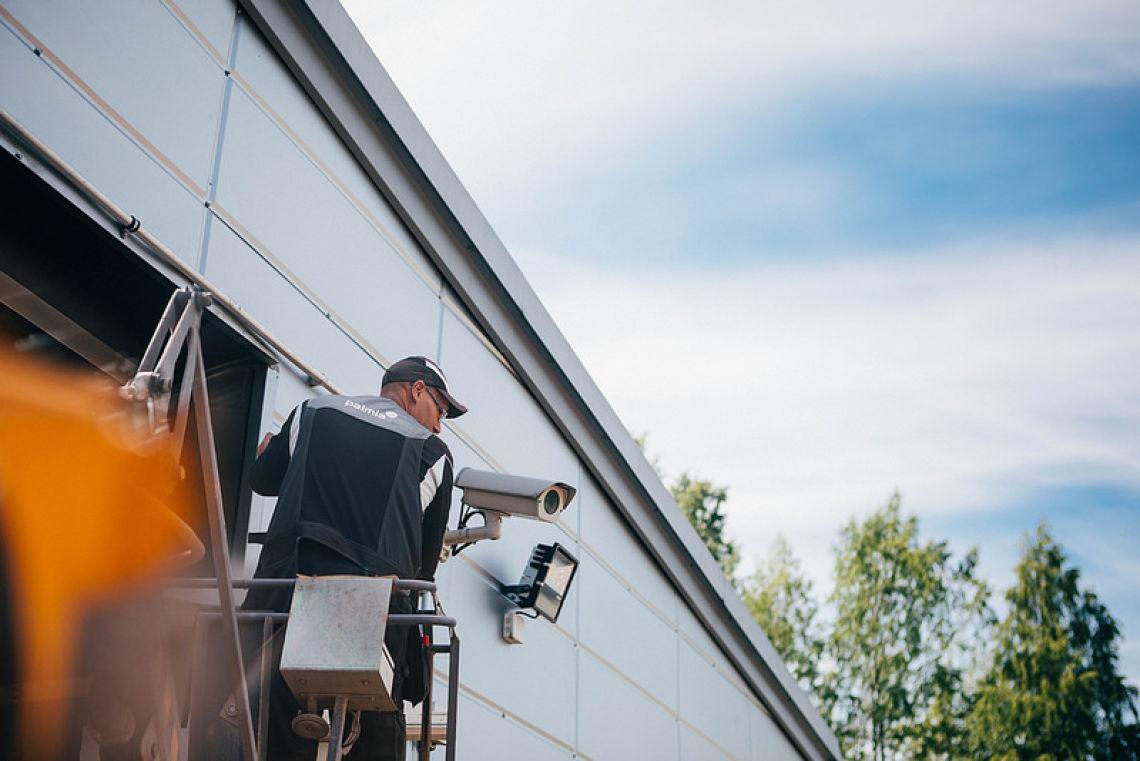 Työntekijä asentaa turvakameraa teollisuushallin oven yläpuolelle.