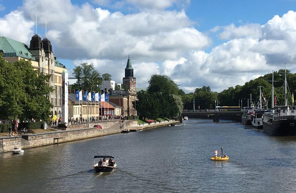 Maisema Turun Aurajoesta, jossa muutama veneilijä liikkuu.